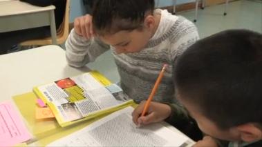 Une étudiante entrain de lire et un autre étudiant entrain d'écrire.