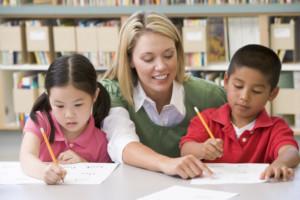 Deux élèves qui écrivent et une enseignante