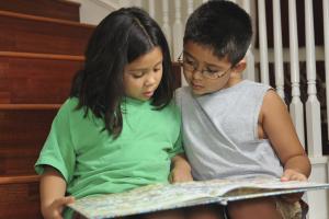 Une fille et un garçon lisent un livre