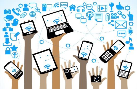 des mains tenant différents appareils technologiques