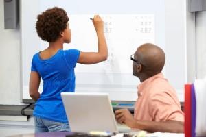 Une élève qui écrit au tableau blanc interactif