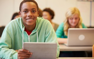 un jeune en classe avec sa tablette