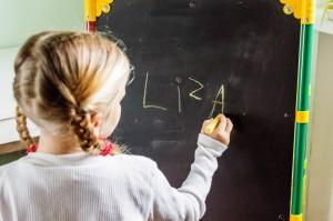 Enfiant qui écrit son nom au tableau noir
