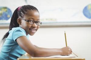 Une élève en train d'écrire à son pupitre