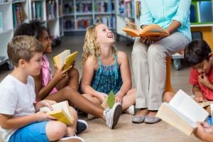Une enseignante et des élèves lisant dans un cercle