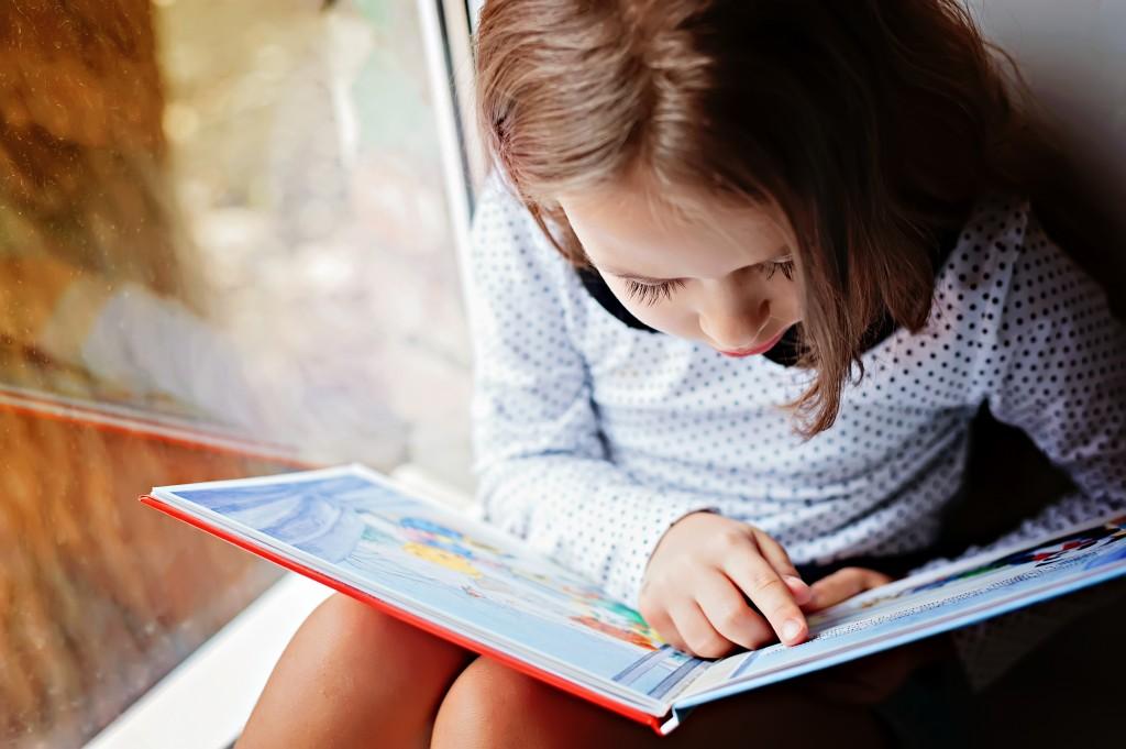 Enfant qui lit en pointant avec le doigt