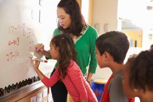 Une enseignante et deux élèves travaillant au tableau blanc