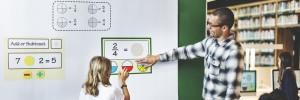 Un enseignant et une élève qui utilisent du matériel de manipulation virtuel sur un tableau blanc interactif